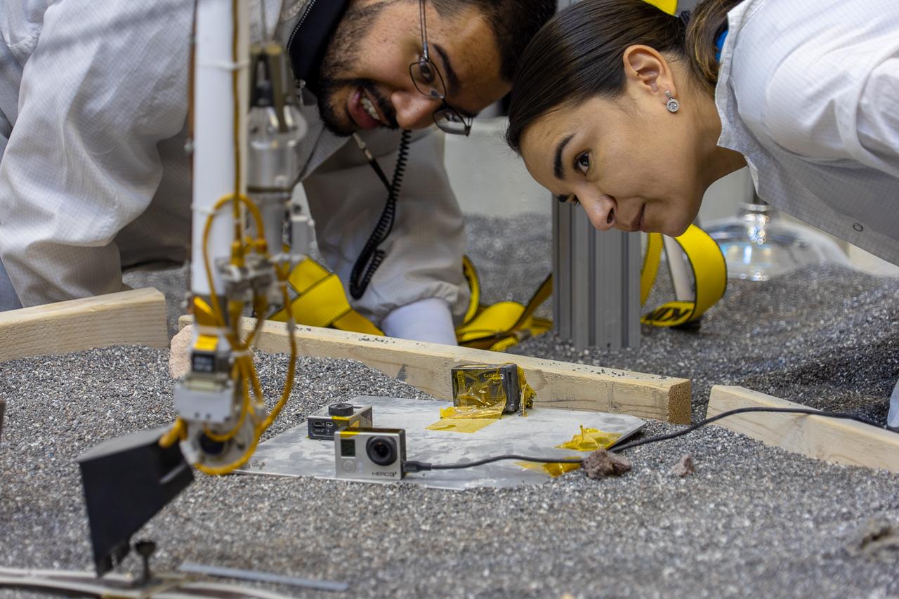 Les ingénieurs Pranay Mishra (à gauche) et Marleen Sundgaard (à droite) surveillent un test d'ajustement de la position de la pinning mass du câble SEIS sur le banc de test ForeSight du Jet Propulsion Laboratory (© NASA/JPL-Caltech/IPGP/Philippe Labrot).