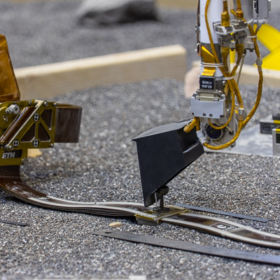 Test d'ajustement de la pinning mass avec la pelle du bras robotique sur le banc de test ForeSight du Jet Propulsion Laboratory (© NASA/JPL-Caltech/IPGP/Philippe Labrot).